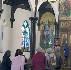 Visitors enjoying a large icon of the Archangel Michael.